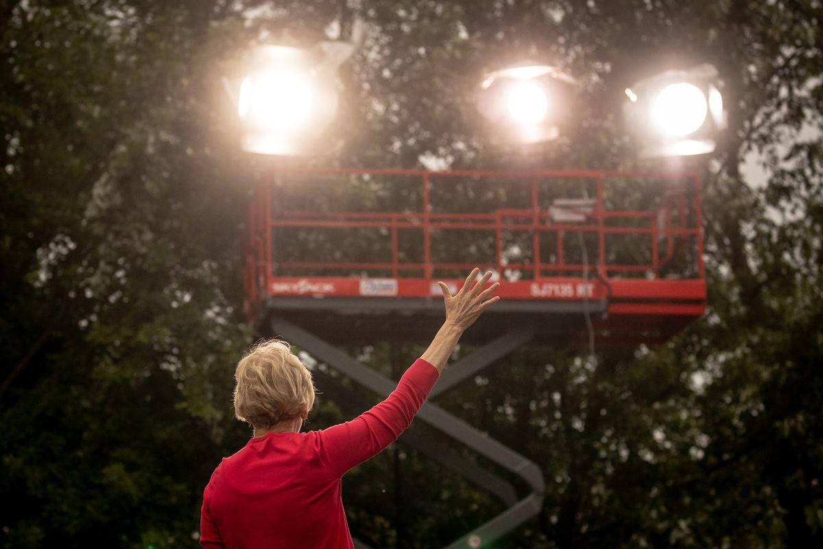 Elizabeth Warren as seen from behind waving toward a cherry picker with floodlights.