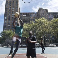 Eric Johnson, left, 19, and Mario Volcin, 23, play basketball in the Jackie Robinson Playground as the Ebbets Field apartments looms in the background, on Wednesday, Sept. 19, 2012 in Brooklyn, N.Y.  Ebbets Field, home to the Brooklyn Dodgers baseball decades ago, became a sprawling residential complex to thousands after the Dodgers moved west.  Now Brooklyn is hitting the major leagues again with a new arena and the Brooklyn Nets' NBA franchise.