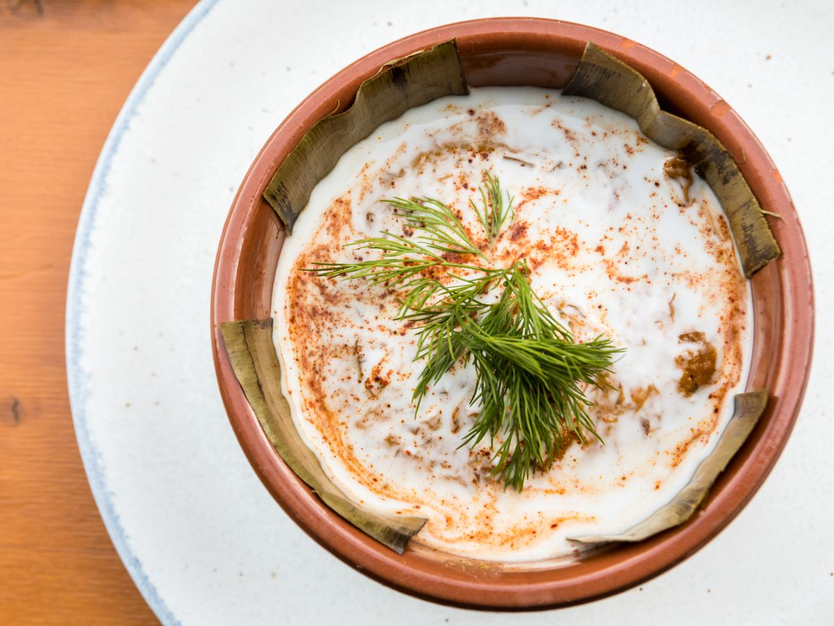 From above, a clay bowl with a thick layer of spice-stained custard and chopped herbs, sitting on a white plate on a wooden tabletop