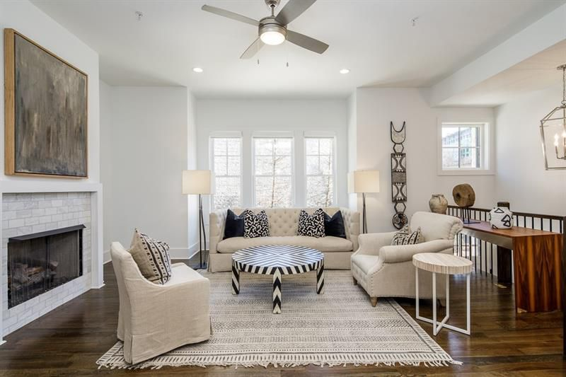 A white-walled living room area with a ceiling fan.