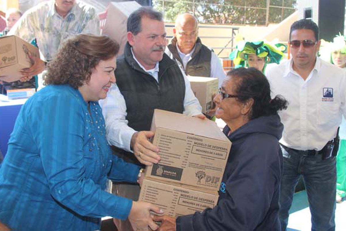 Alejandro Higuera Osuna , the mayor of Mazatlán, Mexico, and his wife, the city's family assistance director  Juana Guillermina Higuera Avila, provide food boxes to a woman.
