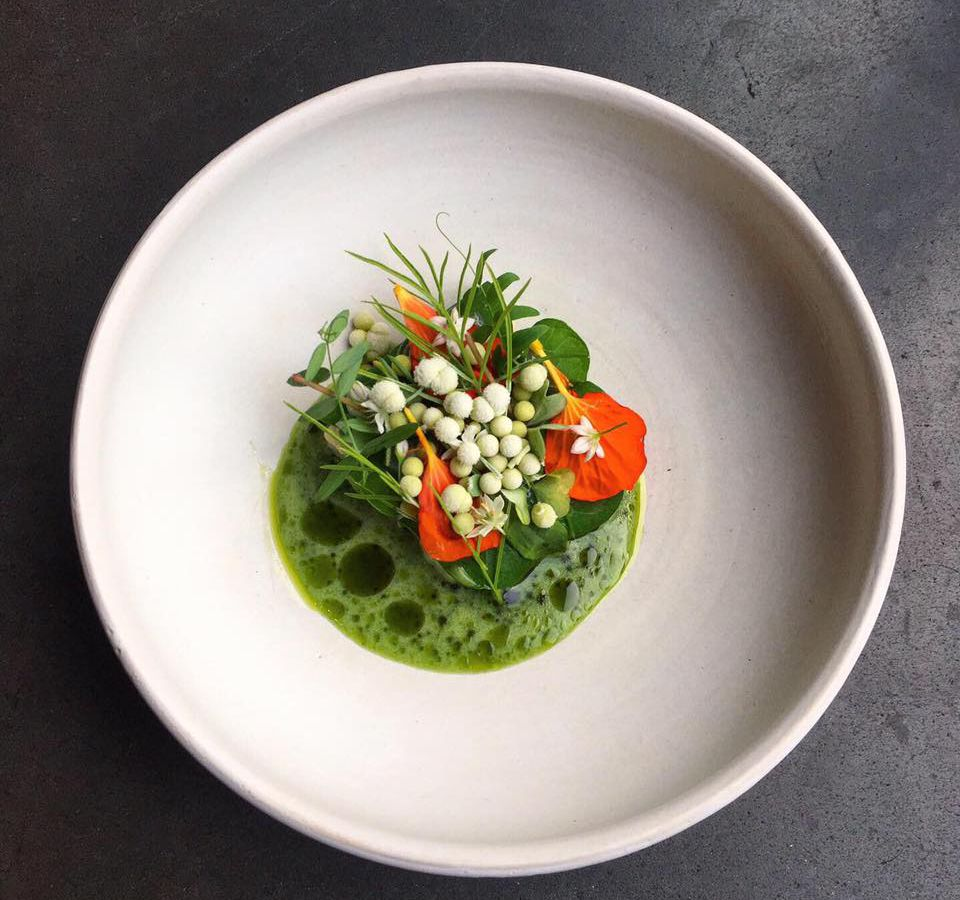 As seen from above, what looks to be a bundle of wild flowers and leaves atop a small pool of broth in a ceramic plate.
