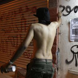 """A Bahraini protester writes the word """"steadfast"""" on a wall with other anti-government graffiti during a demonstration Sunday, April 8, 2012, in the capital of Manama, Bahrain, in support of jailed hunger-striker Abdulhadi al-Khawaja. Bahrain on Sunday rejected the Danish government's request to transfer the jailed activist who is on a nearly two-month hunger strike to Denmark for treatment, the official news agency in the Gulf kingdom said."""