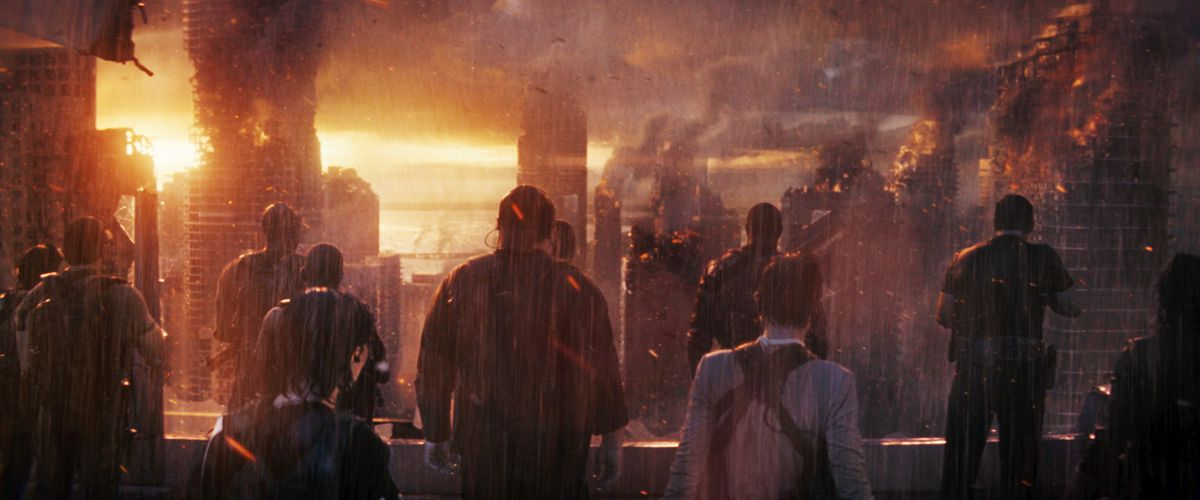 A handful of people, seen from behind, stand in torrential CGI rain and look out at a burning CGI city in The Tomorrow War