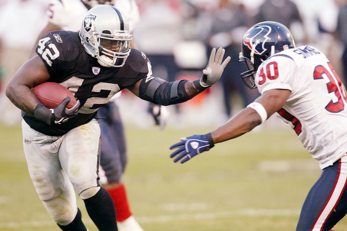 Raiders' ReShard Lee carries as he's covered by Houston's Jason Simmons during a game against the Houston Texans at McAfee Coliseum on Sunday, Dec. 4, 2006, in Oakland, Calif. (Jane Tyska/The Oakland Tribune)
