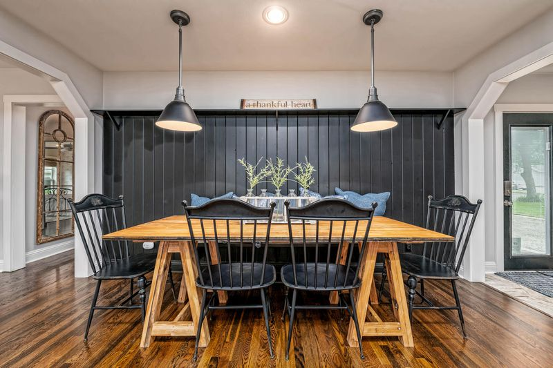 A dining room has a wood table with four black chairs and a black accent wall.