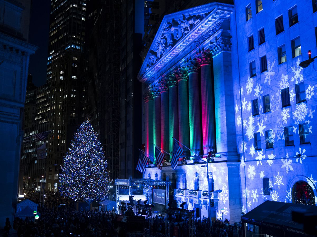 The New York Stock Exchange Christmas Tree. The tree is decorated with lights and sits across from the New York Stock Exchange building which is illuminated in red and green light.