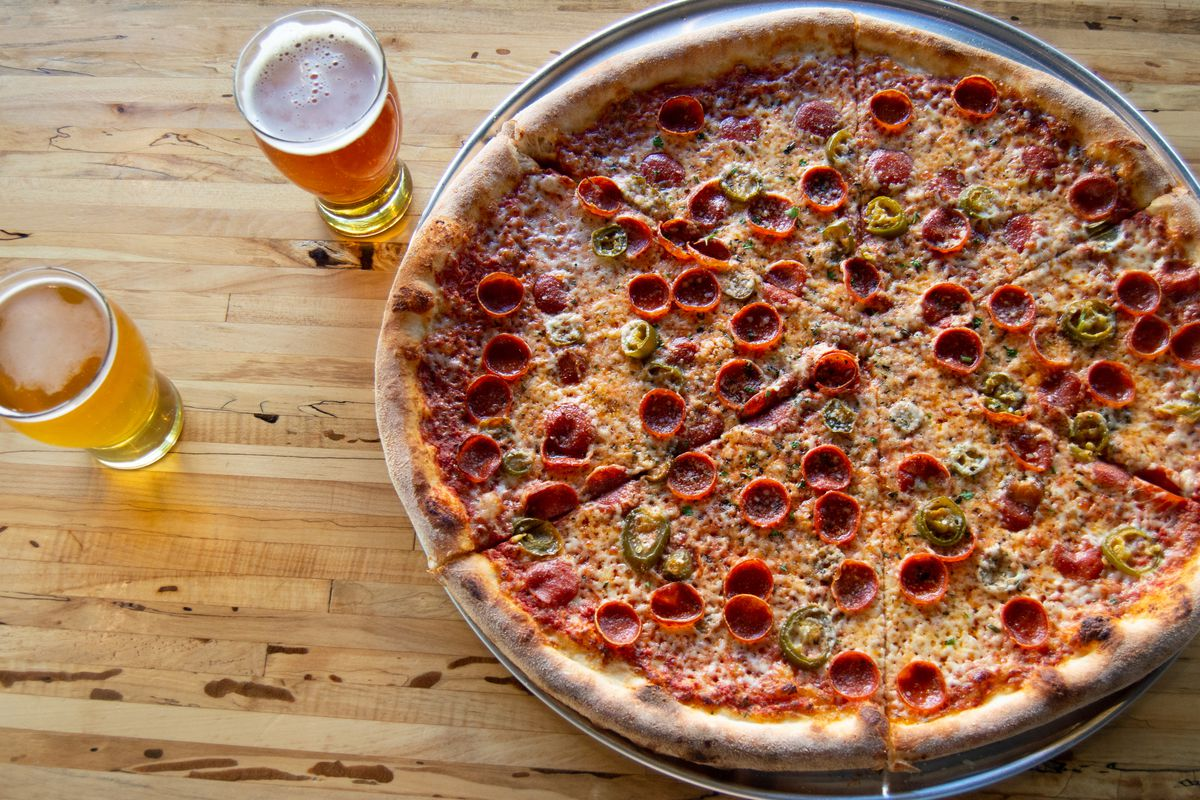 A whole pepperoni pizza sits on a light wood table next to two glasses of beer