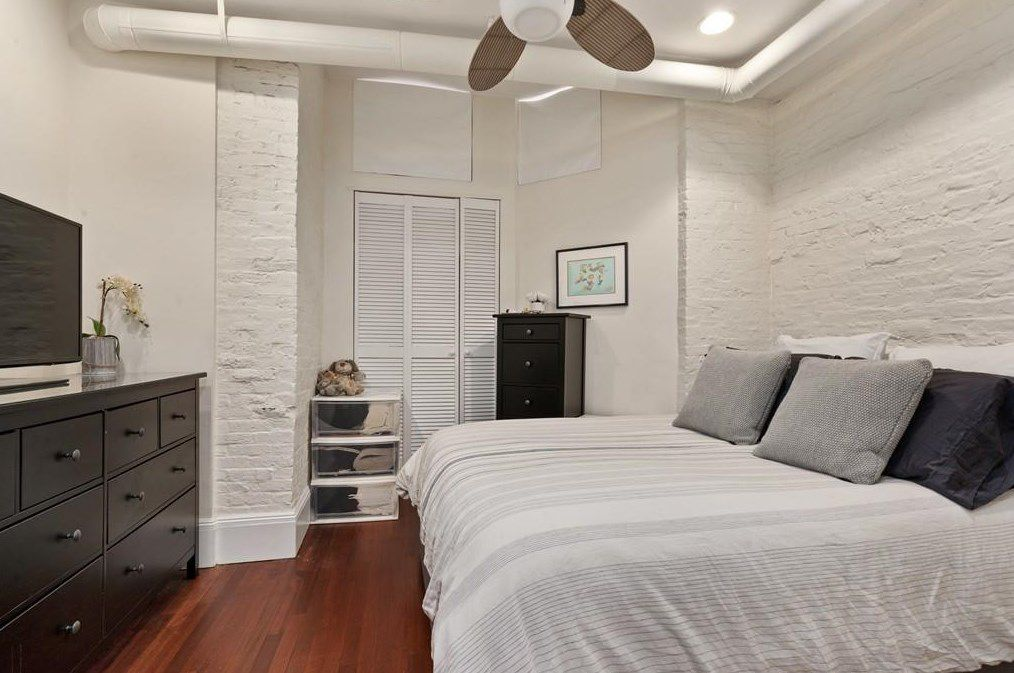 A bedroom with a bed facing a dresser with a TV, and there's a ceiling fan over the bed.