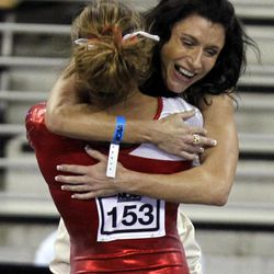 Arkansas' Katherine Grable hugs co-head coach Rene Cook after competing in the balance beam during the semifinals of the NCAA women's gymnastics championships on Friday, April 20 2012, in Duluth, Ga.