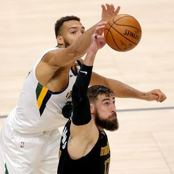 Utah Jazz center Rudy Gobert (27) knocks the ball away from Memphis Grizzlies center Jonas Valanciunas (17) as the Utah Jazz and the Memphis Grizzlies play in game one of their NBA playoff series at Vivint Arena in Salt Lake City on Sunday, May 23, 2021. Memphis won 112-109.