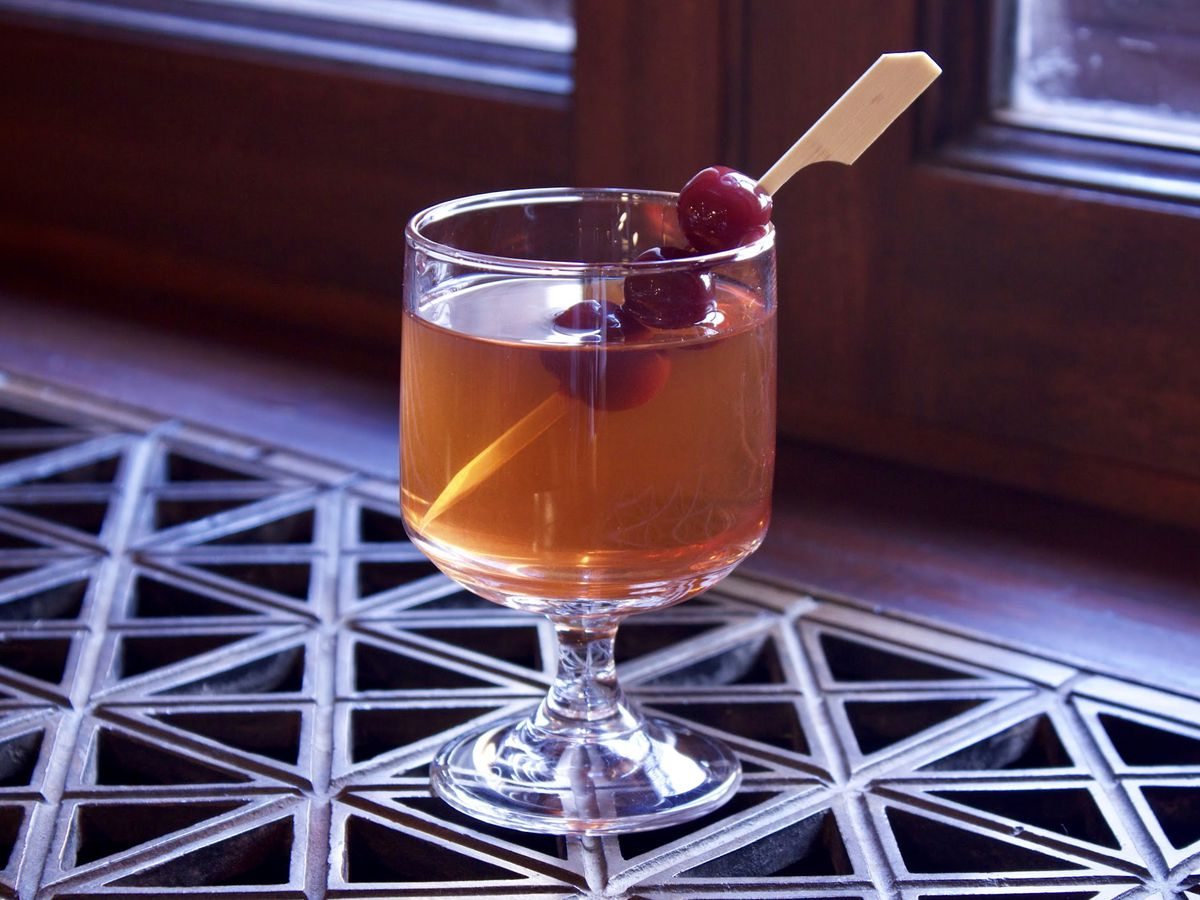 A clear glass filled with a brown cocktail .