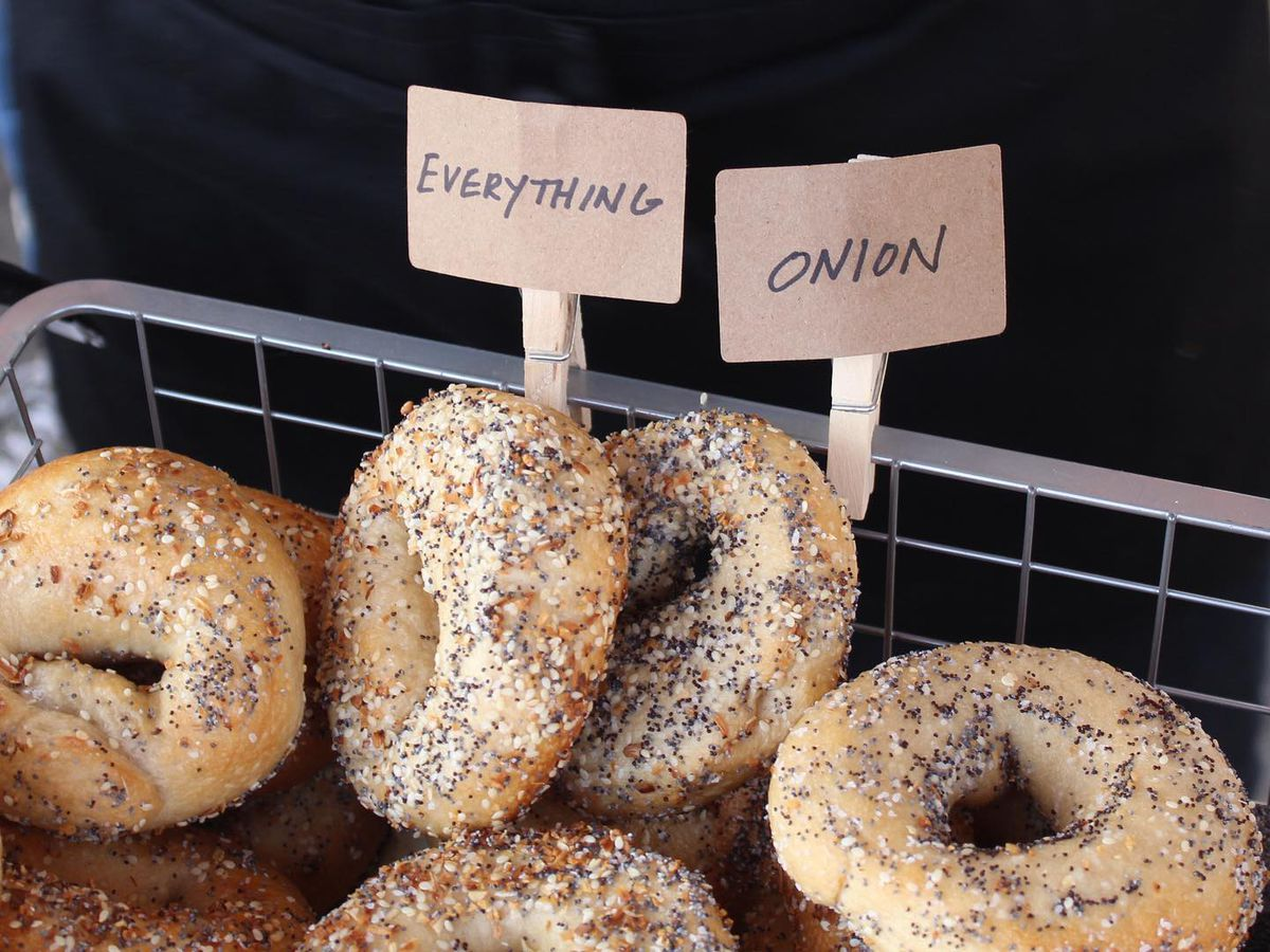 """Metal bins filled with bagels. Two signs say they're """"everything,"""" and """"onion."""""""