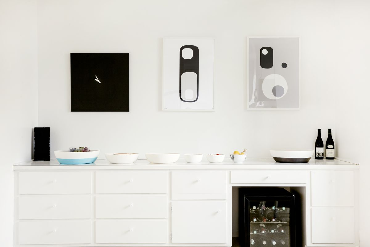 A white cabinet with very minimal bowls on top and some black and white art on the wall above.