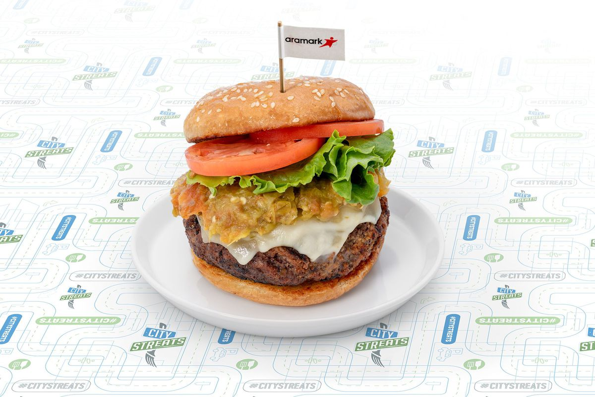 A photo of the new Federal Boulevard Burger, which consists of a patty topped with white pepperjack cheese and a yellow green chili chutney sauce as well as lettuce and tomato on a light brown bun