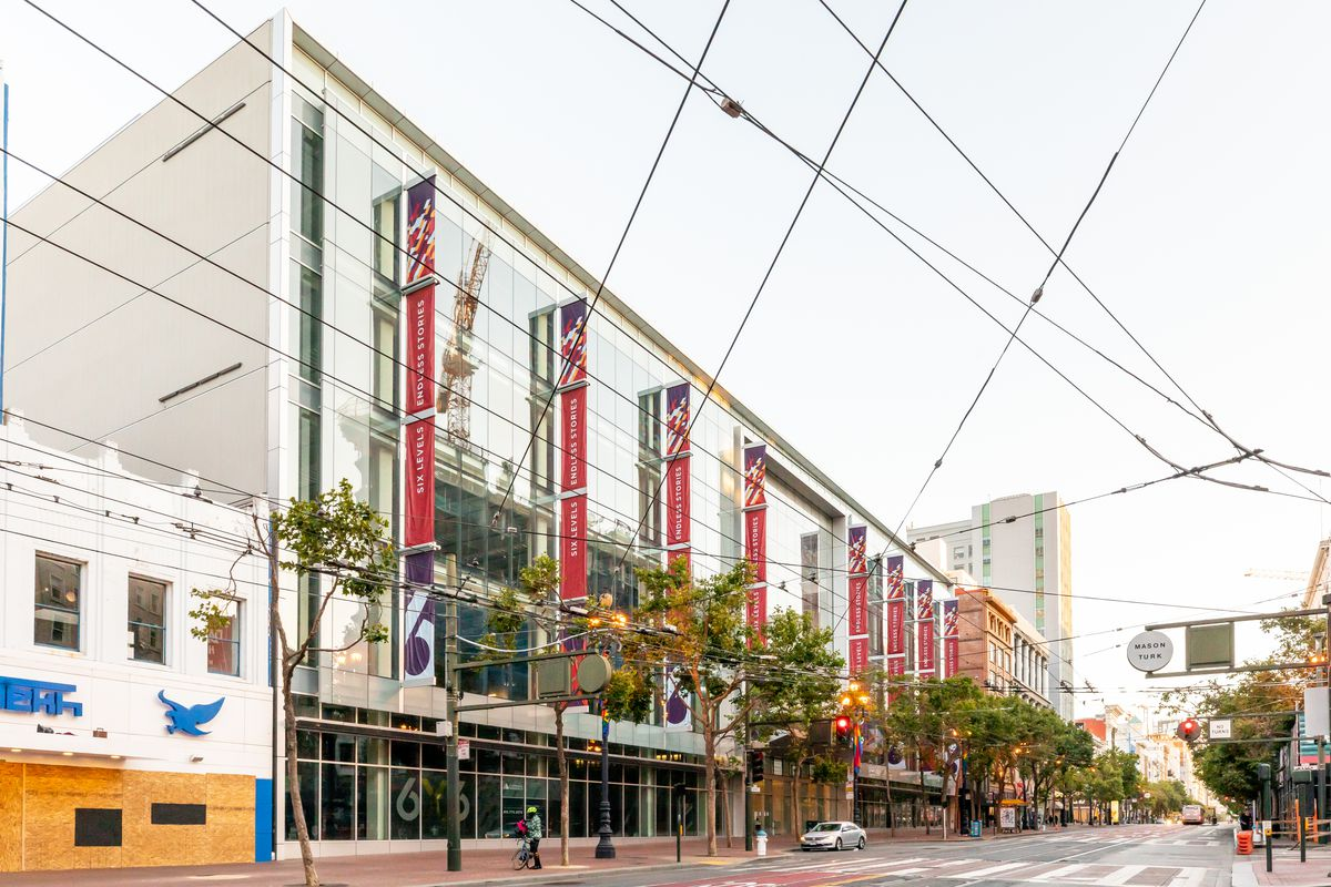 An exterior view of 6x6, a shopping mall in San Francisco with red banners alongside the outside. There are street car lines outside the building, and the dead mall has been empty for four years.