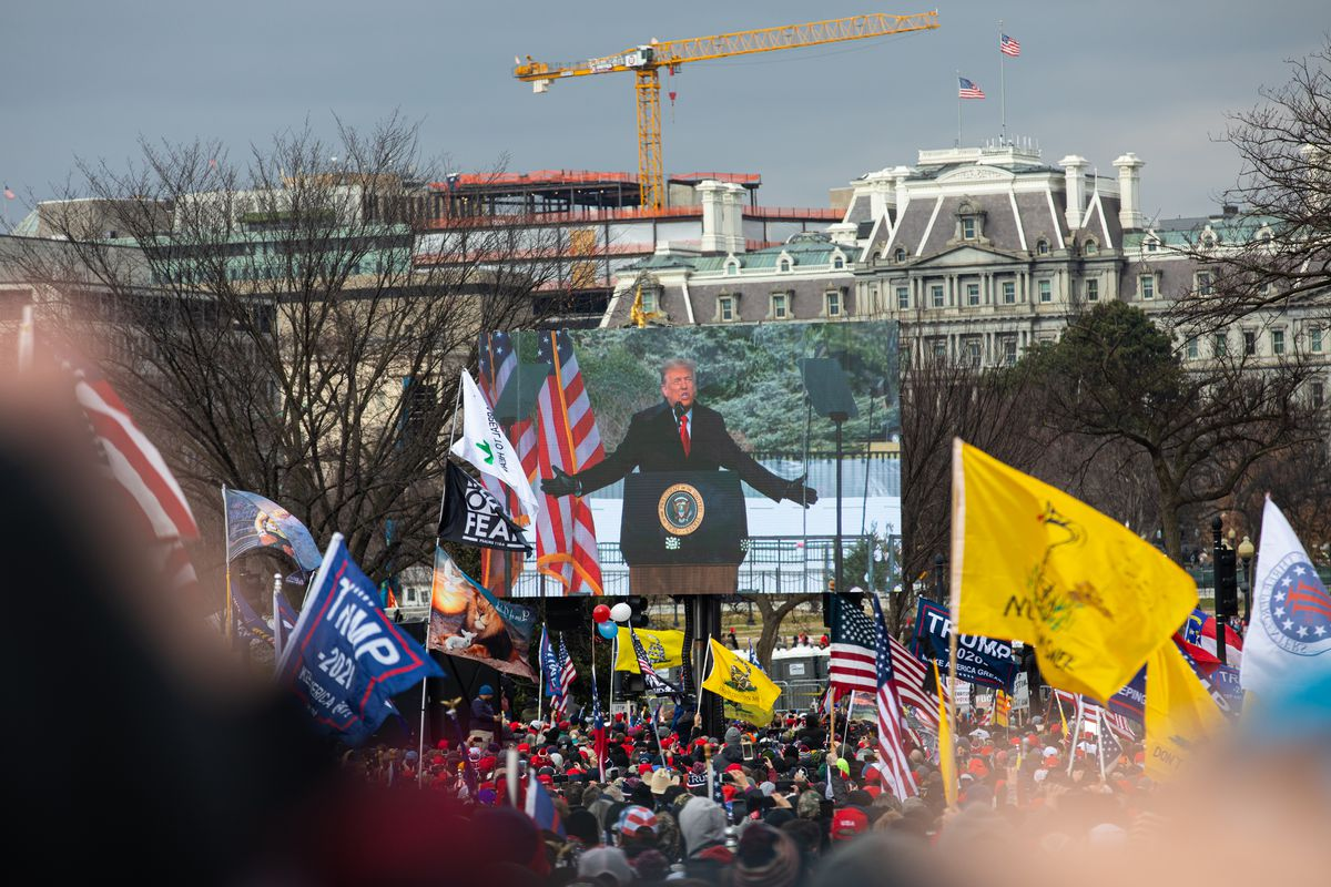 Trump, seen on a giant flatscreen suspended over a large audience — many waving Trump, QAnon, and alt-right flags — stands behind a podium featuring the seal of the president of the United States; dressed in a dark coat and red tie, his arms are spread wide as he speaks emphatically into a microphone.