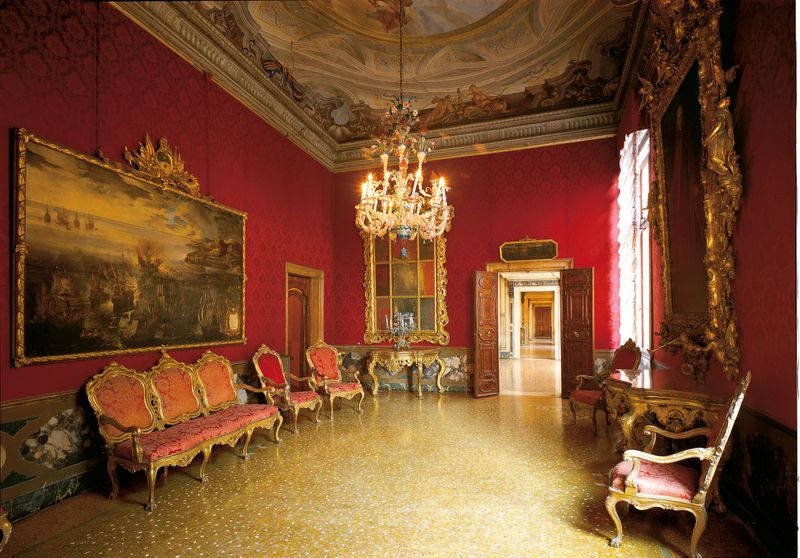 A Venetian palace room interior complete with gilt-edged frames, chandelier, frescoed ceiling, and a terrazzo floor.