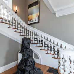 """The home's foyer, staircase, and 1st and 2nd floor hallways were designed by Alex Ray of Five Sense Art Consultancy. Above is a black lava sculpture by Darren Waterston. It """"contrasts an unexpected force of nature against the controlled architecture of th"""