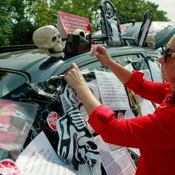 Philomena Johnson, a delegate from Little Village Academy, decorates her vehicle to highlight the need for increased social services in schools before attending a meeting of the Chicago Teachers Union delegates Sunday, Sept. 16, 2012 in Chicago. Hundreds of CTU delegates are expected to review a proposed contract and vote on whether to suspend the teachers strike which has kept more than 350,000 students out of school since Monday.