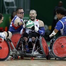 United States' Josh Wheeler, center, fights for the ball with France's Riadh Sallem, right, and Christophe Salegui during a mixed wheelchair rugby group B game at the Paralympic Games in Rio de Janeiro, Brazil, Wednesday, Sept. 14, 2016.