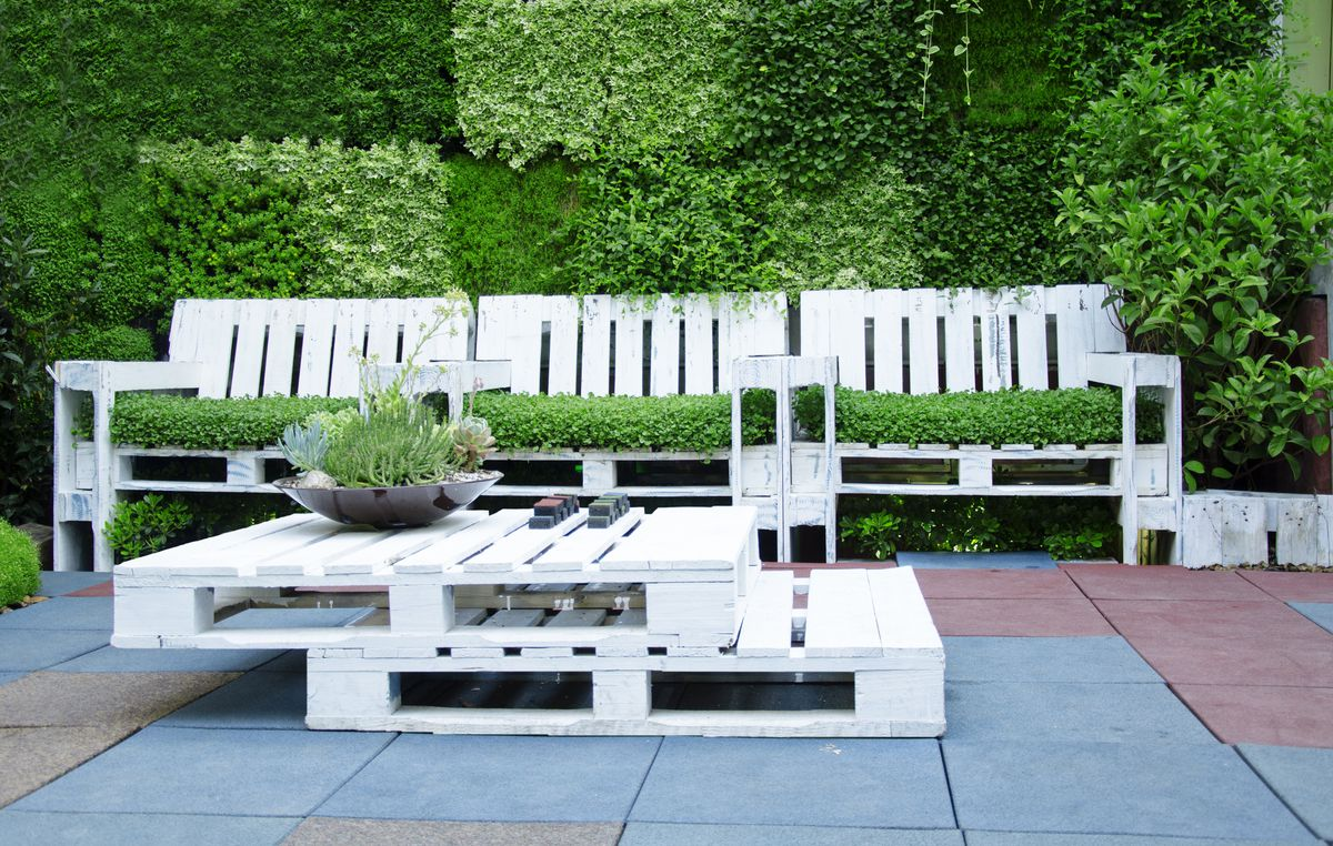 An outdoor patio with white patio furniture. There is a table, bench, and a planter with flowers.