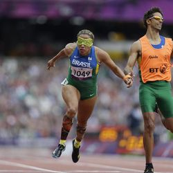 Brazil's Terezinha Guilhermina, along with her guide Guilherme Soares de Santana, competes during a women's 200m T11 round 1 race at the 2012 Paralympics in London, Saturday, Sept. 1, 2012.