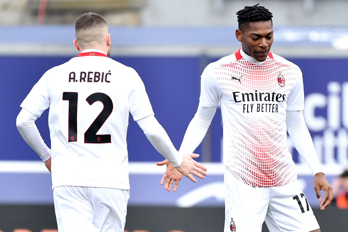 Ante Rebic and Rafael Leao of AC Milan greet each other...
