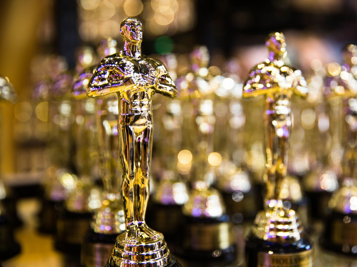 Rows of Oscar statuettes on a glass table.