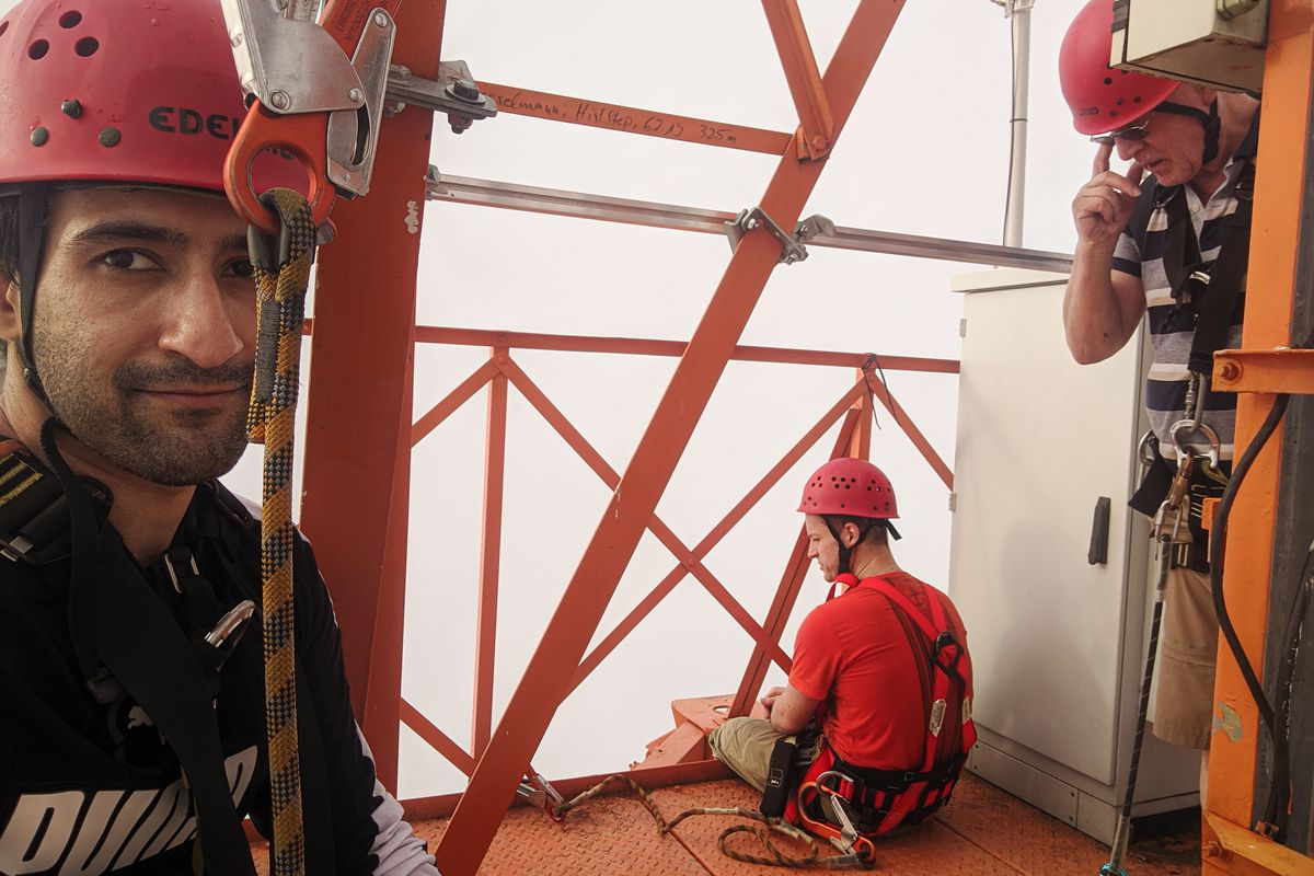 The reporter is seen with helmets and safety equipment at the top of the Amazon Tall Tower Observatory.