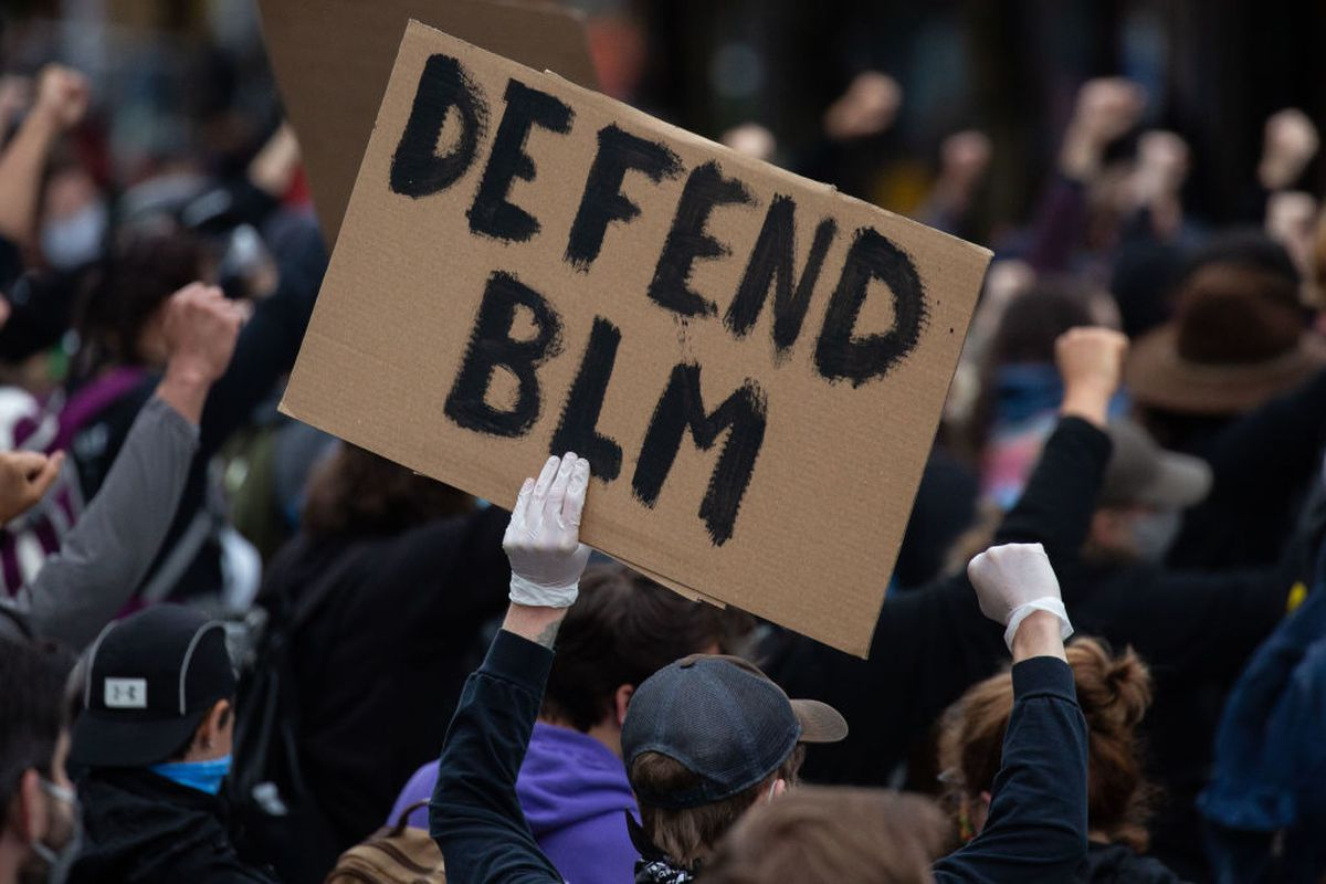 """A Seattle protester with a gloved hand holds up a sign that says """"Defend BLM."""""""