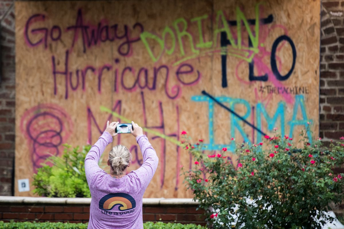 """A woman takes a picture of graffiti on a plywood board tacked up due to the impending arrival of a hurricane that reads, """"Go away, Hurricane Dorian,"""" with the names of other hurricanes —Flo, Irma, Maria — crossed out."""
