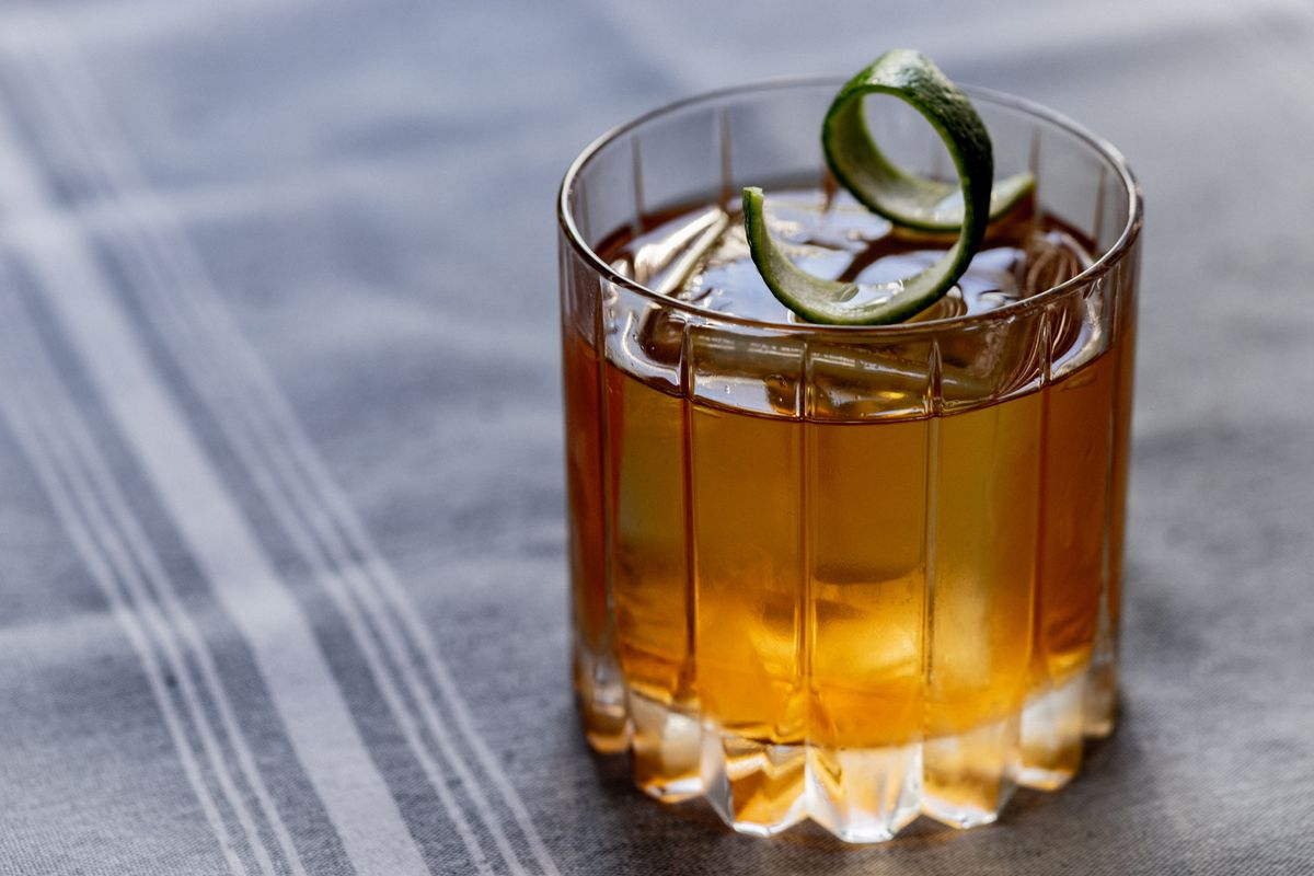 A close up photo of the rum-based Mariner in a rocks glass garnished with a lime peel