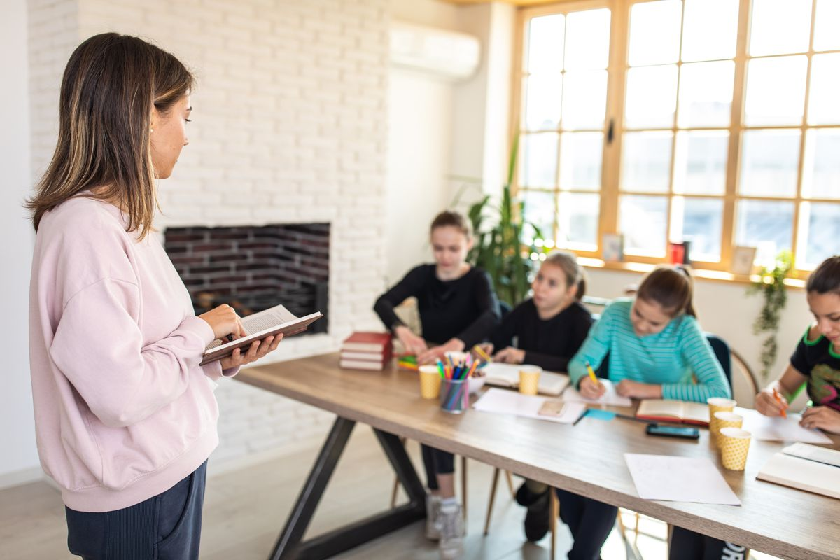 Image of teacher teaching a small group of students inside a home.