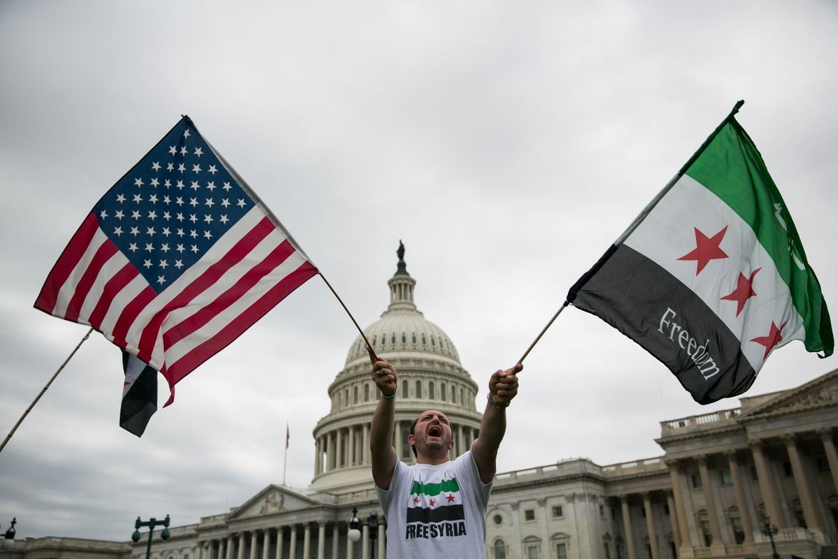 Jehad Sibai waves flags during a rally on Capitol Hill in support of possible US military action in Syria on September 9, 2013, in Washington, DC.