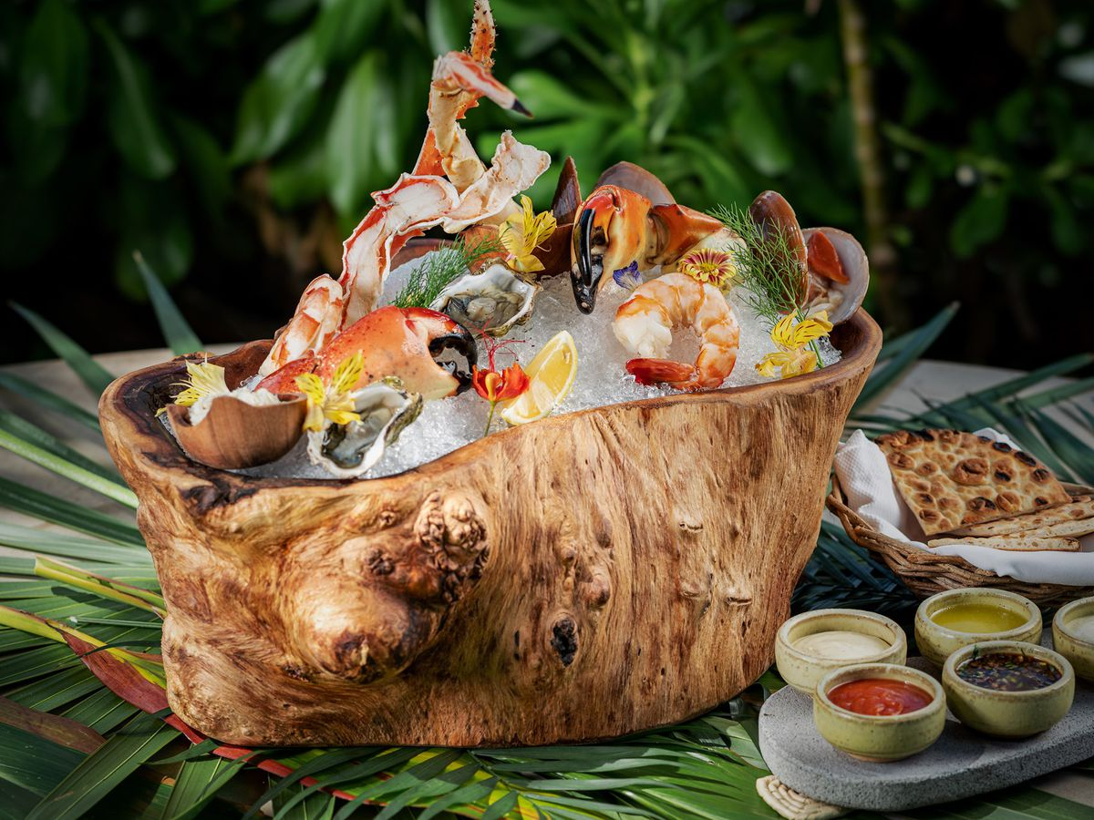 Raw seafood variety served on ice in a large tree stump, beside sauces and condiments on a palm-laden table