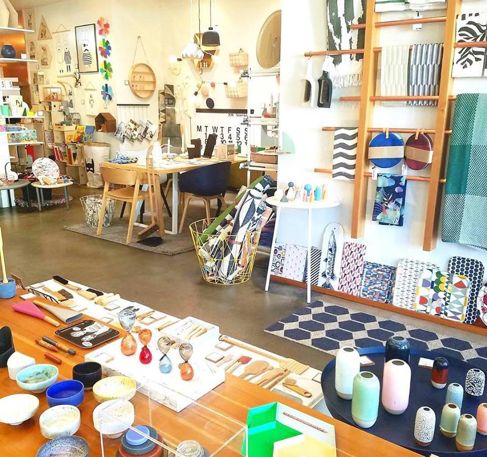The interior of a furniture store. There are many items of furniture and various decorative items in a room. There is a blue and white polkadot area rug.