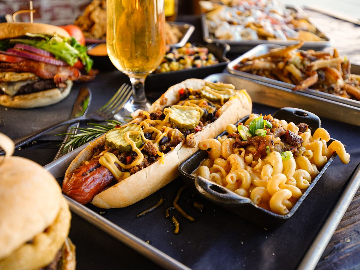 A tray with a large hot dog topped with chili and cheese, next to a cast iron tray of mac and cheese, beside other burgers, sandwiches, and drinks on a wooden table