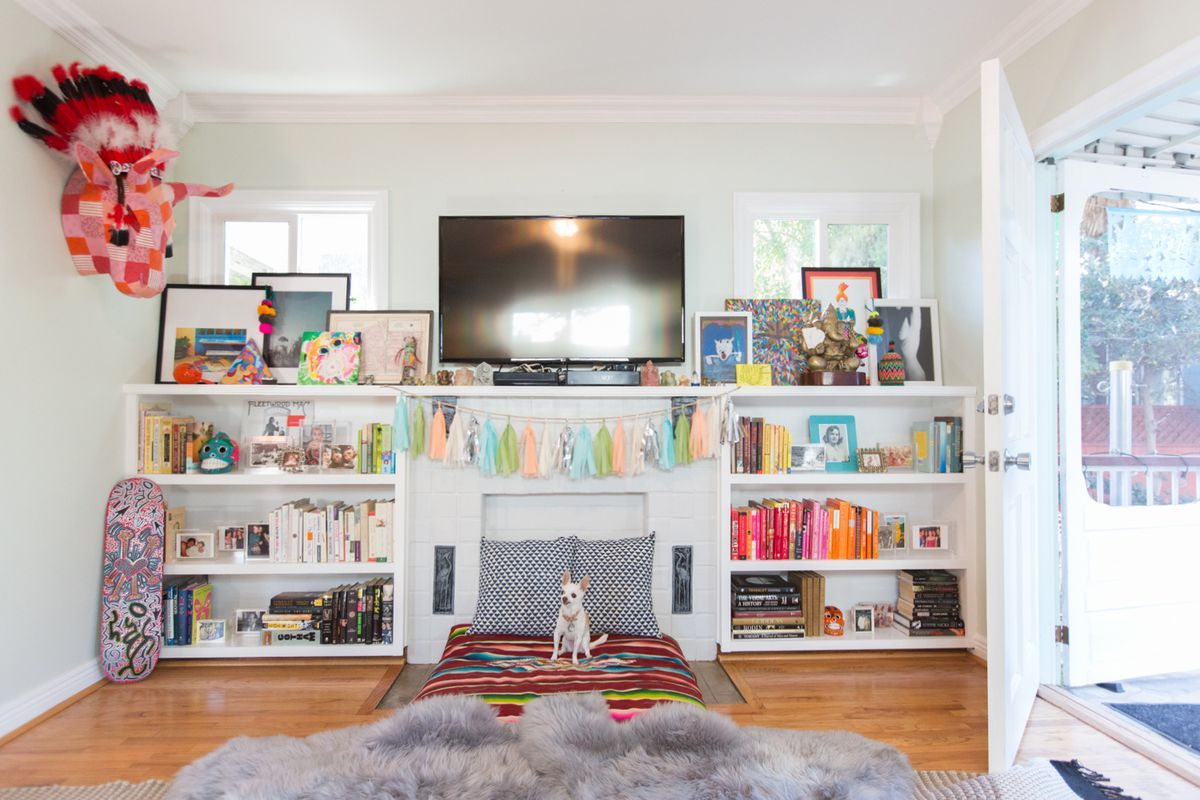 Built-in bookcases hold a collection of books, photos, and framed art pieces. A small white chihuahua sits on a large patterned pillow on the floor.