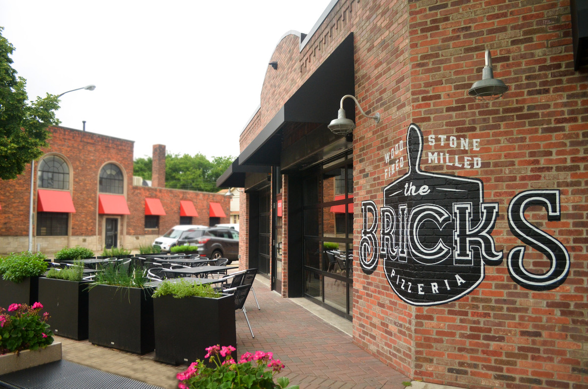 the brick corner building that houses The Bricks features silver exterior lamps and black awnings above garage-door style windows leading out to a patio.
