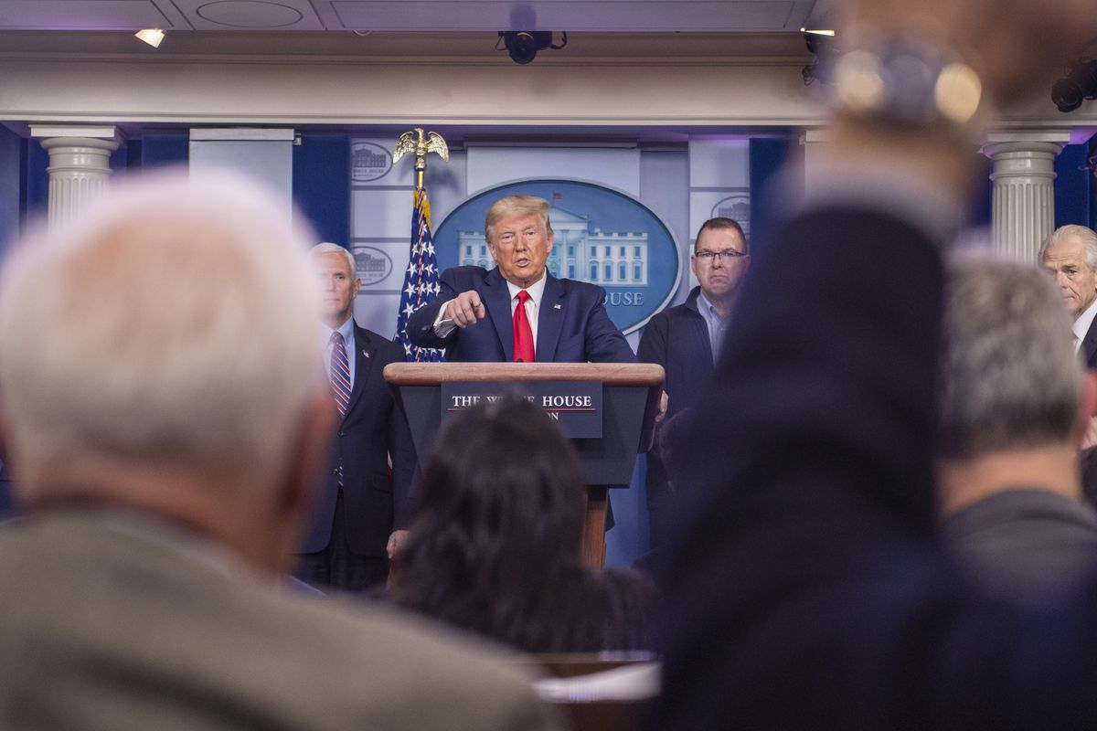 A wide shot of the president in a dark suit and red tie, illuminated by a spotlight in the White House briefing room, pointing to reporters. In the foreground, journalists have their hands raised, framing Trump.