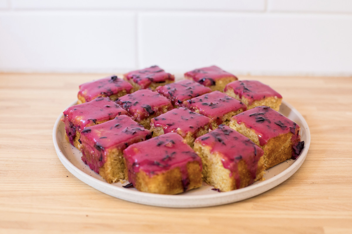 A blueberry-glazed cornbread cake sliced into squares sits on a plate on a blonde-wood surface.