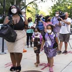 A mother and her daughters walk into school at Mary E. Courtenay Language Arts Center at 4420 N Beacon St. in Uptown, Monday, Aug. 30, 2021.