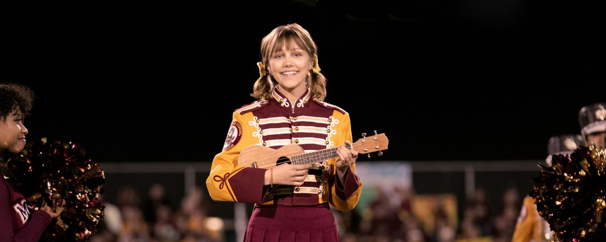 stargirl strumming a ukulele on the football field in a marching band uniform