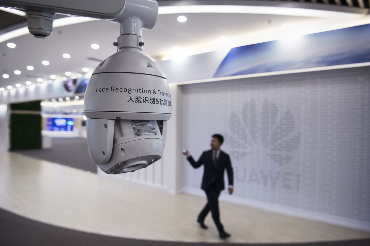 """A surveillance camera hanging over a man on a stage in front of a backdrop reading """"Huawei."""""""
