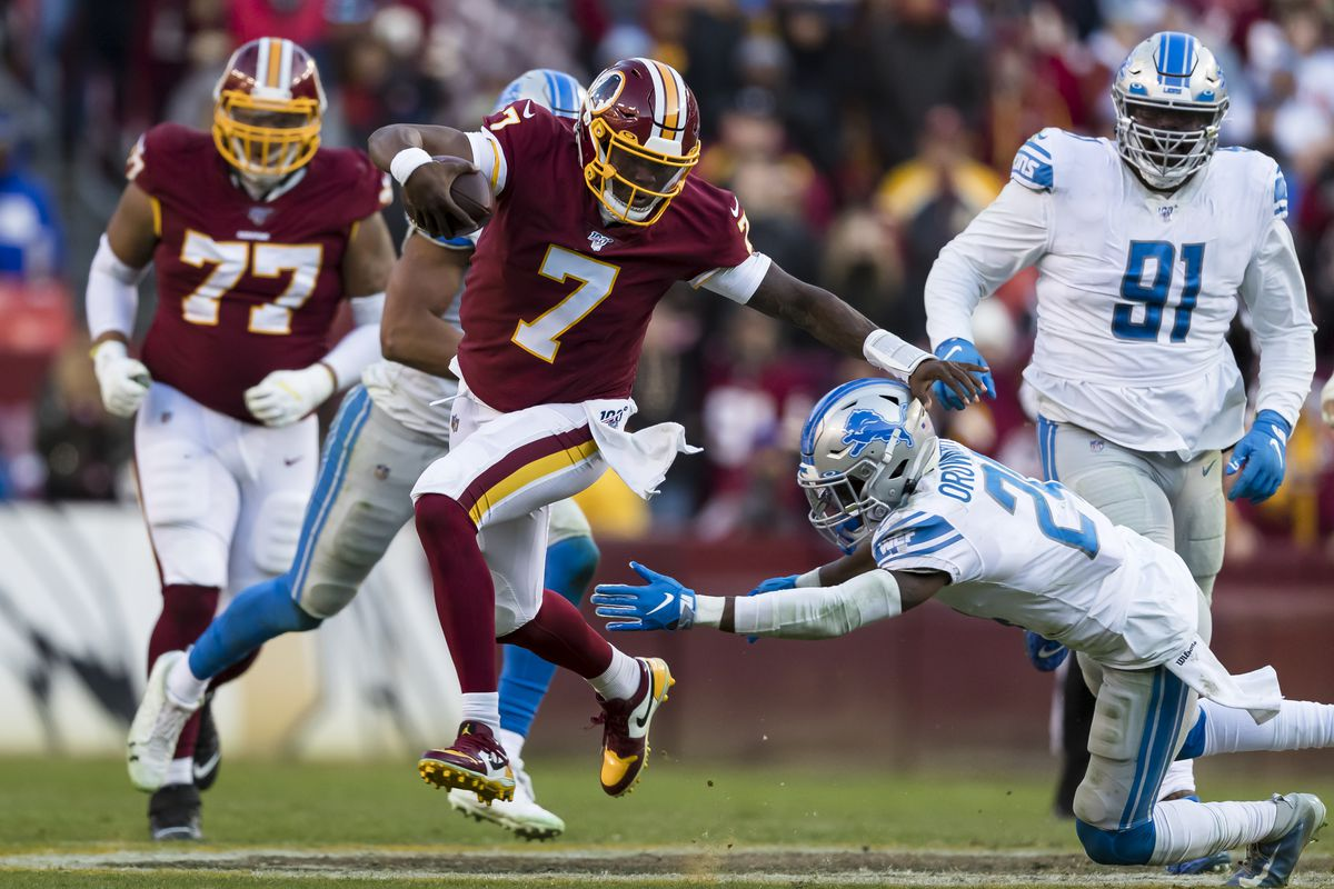 Washington QB Dwayne Haskins attempts to avoid the tackle of Amani Oruwariye of the Detroit Lions during the second half at FedExField on November 24, 2019 in Landover, Maryland.