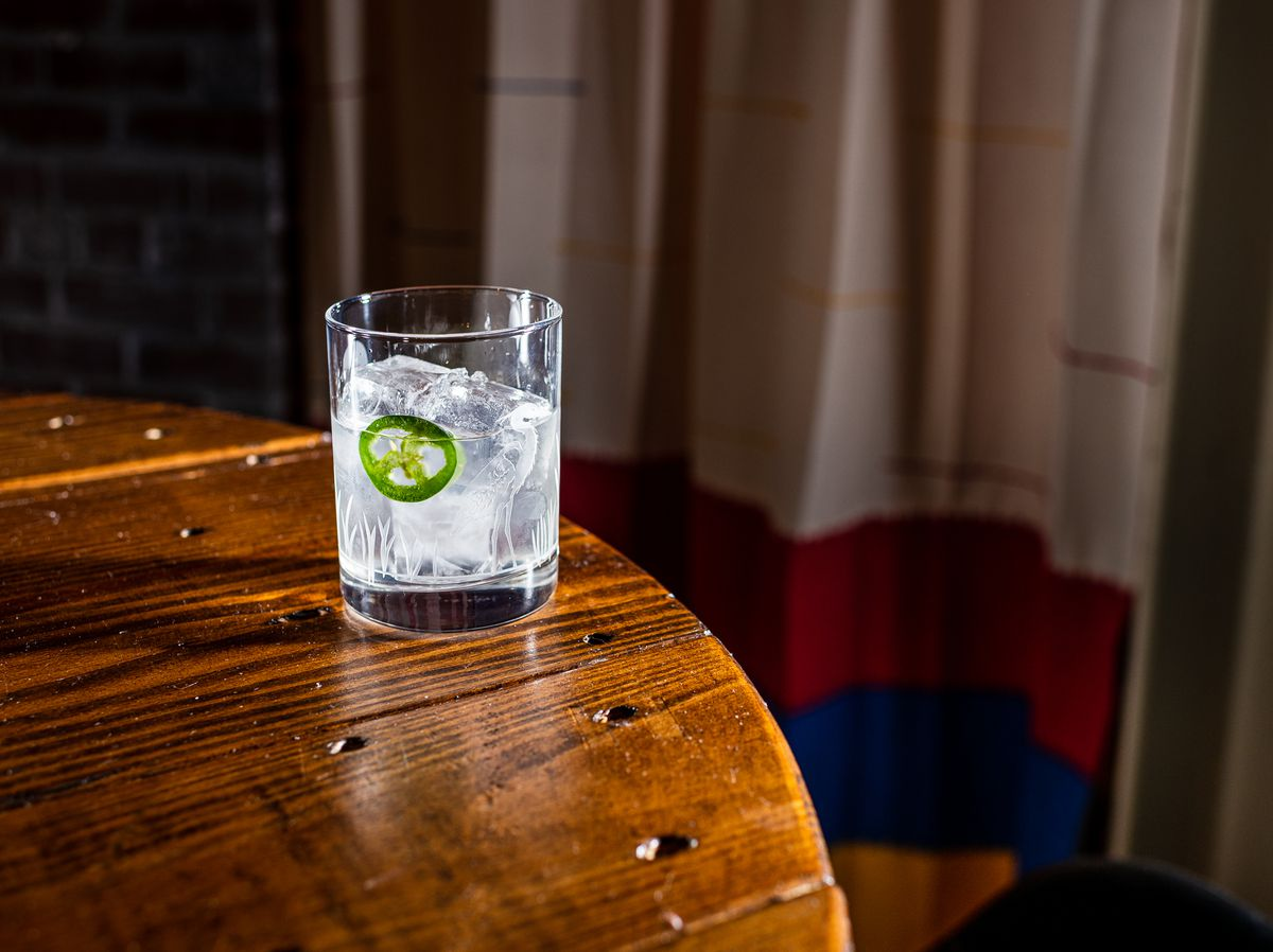 A glass is filled with a clear cocktail, ice, and a jalapeno slice from Chacho