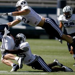 McKay Jacobson gets tackled by Corby Eason and Spencer Hadley during a scrimmage at the LaVell Edwards Stadium at BYU in Provo on Saturday, Aug. 20, 2011.