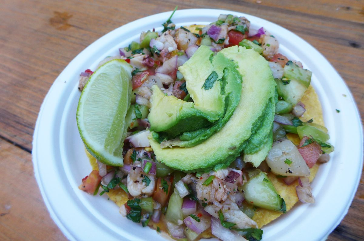 A selection of seafood mounted on a tostada with two slices of green avocado on top.