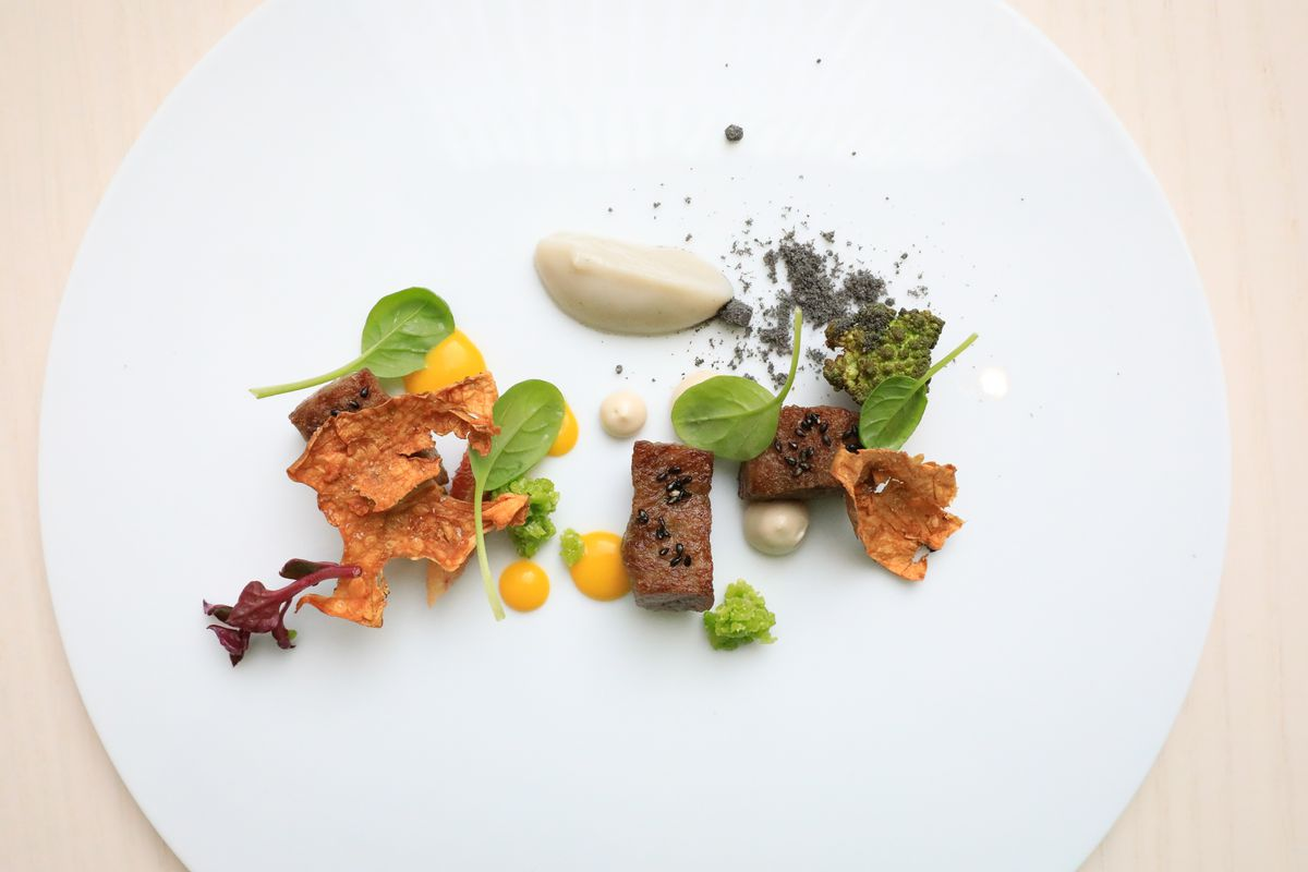 A white plate with artfully arranged Wagyu beef, sunchoke, orange, and tat soi